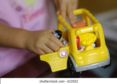 A child plays with a toy school bus
