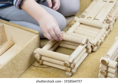 Child plays with a wooden construction set