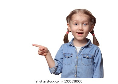 The child is pointing at something. Beautiful girl with pigtails joyfully points a finger upwards. Teenager dressed in a denim shirt.