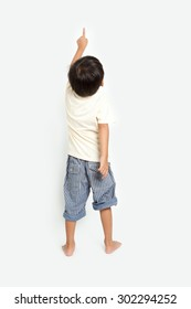 child pointing at wall. Back view. Isolated on white background