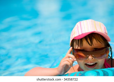 Child in pool wearing sunglasses and cap laughing