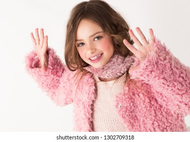 The child poses in the studio, shows his hands with fingers spread.