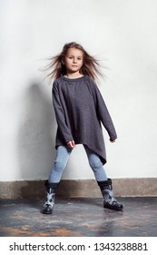 child posing in a stylish, urban, casual clothes. fashion little girl standing near white wall. Portrait young charming fashion kid in leggings, sweater, rubber boots.