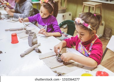 Child pottery workshop, little girl working with clay, creative learning.