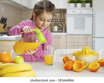 Child pouring fresh made orange juice ready for drinking