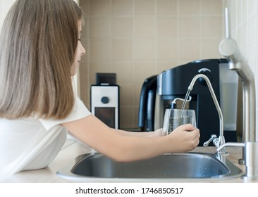 Child pouring fresh reverse osmosis purified water in kitchen at home. Drinking tap water. Consumption of tap water contributes to the saving of water in plastic bottles. Protection of the environment