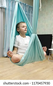 Child practices aerial yoga in a gym
