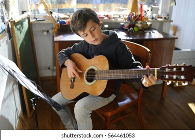 Child is practicing acoustic guitar in his room