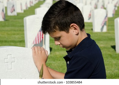 a child praying at a gravesite at a national cemetery in San Diego,CA on Memorial Day.