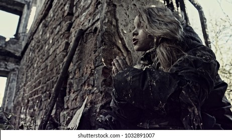 The child prays. Refugee. Apocalypse
