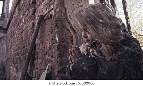 The child prays in ruins.