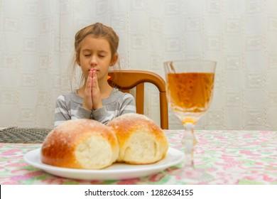 Child prays at Shabbat. Little Jewish Sabbath. Jewish child at the Sabbath table.
