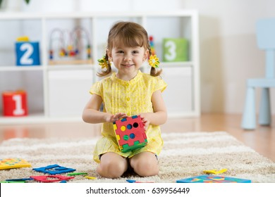 Child preschooler girl plays logical toy learning shapes and colors at home, daycare or nursery