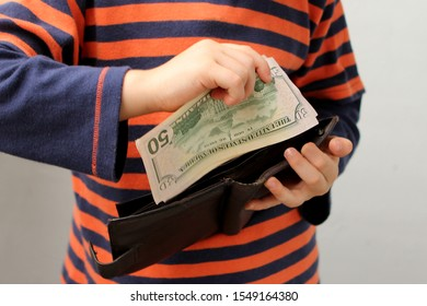 child, preschooler, primary school student, puts money, banknotes, dollars, euros in a leather wallet, hands close-up - Shutterstock ID 1549164380