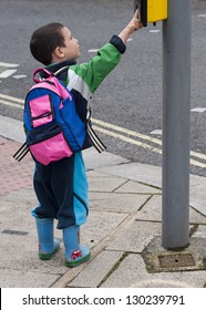 Child pressing a button at traffic lights on pedestrian crossing.