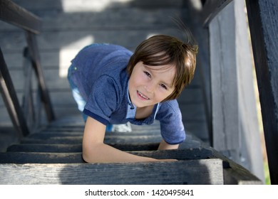 Child, preteen boy, sitting on wooden stairs, outdoor