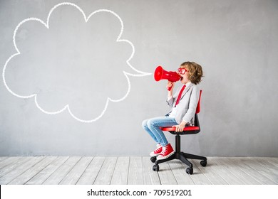 Child pretend to be businessman. Child playing at home. Kid shouting by vintage megaphone. Imagination, idea and start up concept. Speech bubble with copy space for your text