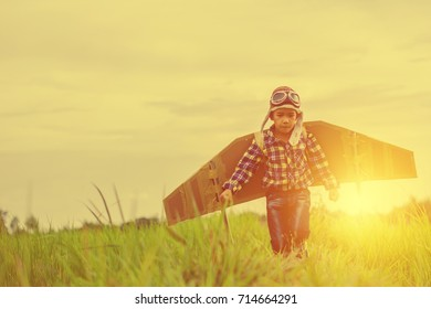Child pretend to be pilot. Kid having fun at outdoor.He used paper to make wings. Summer vacation and travel concept.