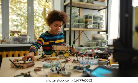 Child programming, testing robot vehicle, working with wires and circuits at stem class. Robotics and software engineering for elementary students. Horizontal shot. Web Banner