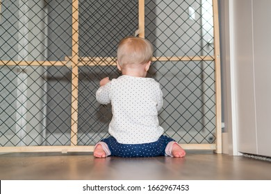 Child Proofing - Cute Baby Playing Behind Safety Gate