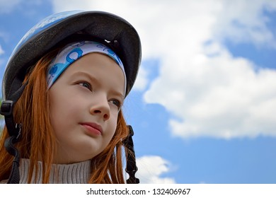 Child in a protective helmet on a background blue sky