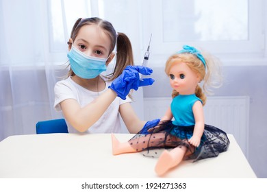 a child in a protective mask and large blue gloves plays doctor, gives a doll a shot with a syringe, the concept of coronavirus and vaccination