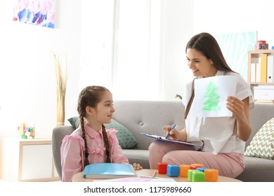 Child psychologist working with little girl in office