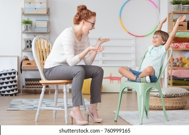 Child psychologist and young kid with ADHD during therapy session in primary school interior