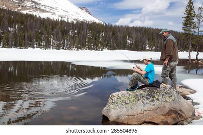 The child pulls a fish from alpine lakes.  Father ready to help.  Mirror Lake,  Uinta-Wasatch-Cache National Forest, Utah