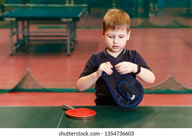 the child pulls out the racket of table tennis cover indoors