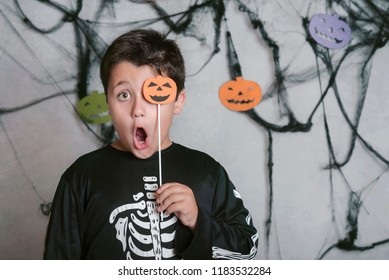 child with a pumpkin covering his eye at halloween party