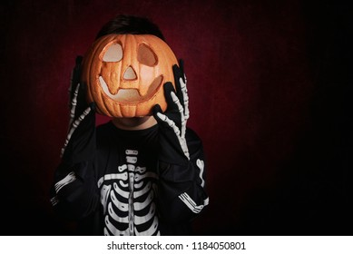 child with a pumpkin covering his face on halloween
