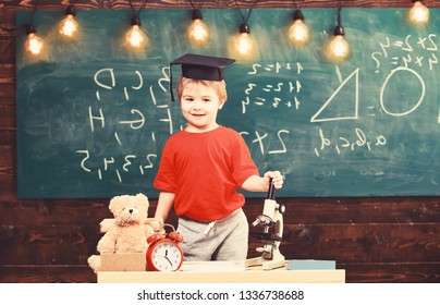 Child, pupil on smiling face near microscope. First former interested in studying, education. Wunderkind concept. Kid boy in graduate cap near microscope in classroom, chalkboard on background.