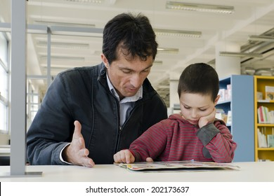 Child pupil with parent or teacher reading a book in public library.