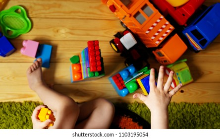 child put forward hand to toys