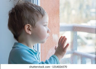 The child put his hand on the windowpane and is surprised to look out the window