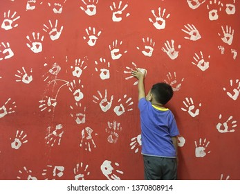 A child puts a hand on a white hand print icon on the red wall.