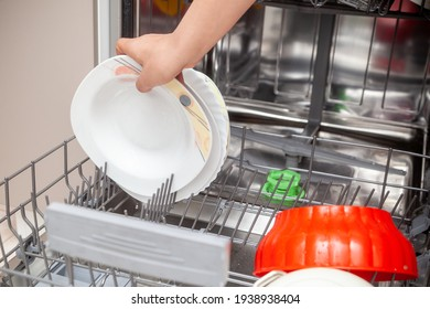 Child putting dishes in dishwasher