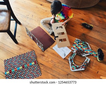 Child putting a gingerbread house together