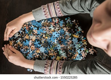 Child and puzzle. Many puzzle pieces in hands.