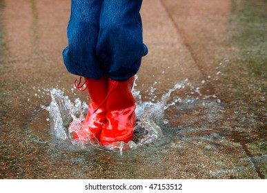 child with rain boots jumps into a puddle