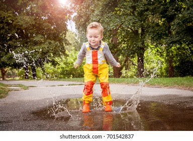 Child in rainy day. Cute happy child boy is jumping in the puddle. Bright autumn rainy day. Kid in orange rubber boots and rain suit, raincoat. Boy outdoors.