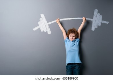 Child raising a barbell with heavy weight. Boy dreaming about getting muscular and becoming sport star.