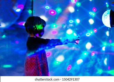 child reaches for light. Girl at party with disco during laser show with colorful rays and neon lighting in blue LED lights room. Baby disco. Selective focus