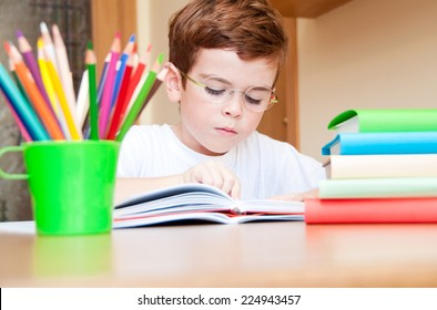 Child reading a book at a desk