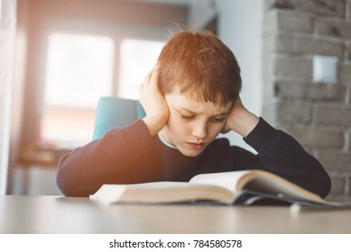 Child reading a book at the desk. 8 years old boy tired doing his homework at the table