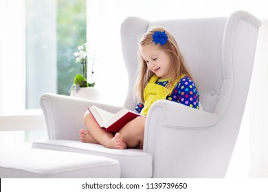 Child reading book. Kids read books. Little girl doing school homework. Preschool kid learning and studying at home. Preschooler in white armchair in white sunny bedroom at home. Children education.