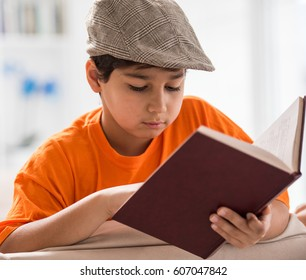 Child reading book on sofa