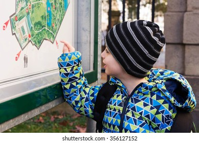 Child reading public map or plan of city park on a board