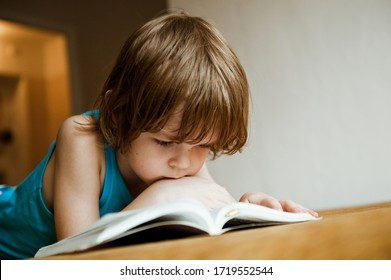 A child reads a book. The boy is lying on the sofa and reading a book.